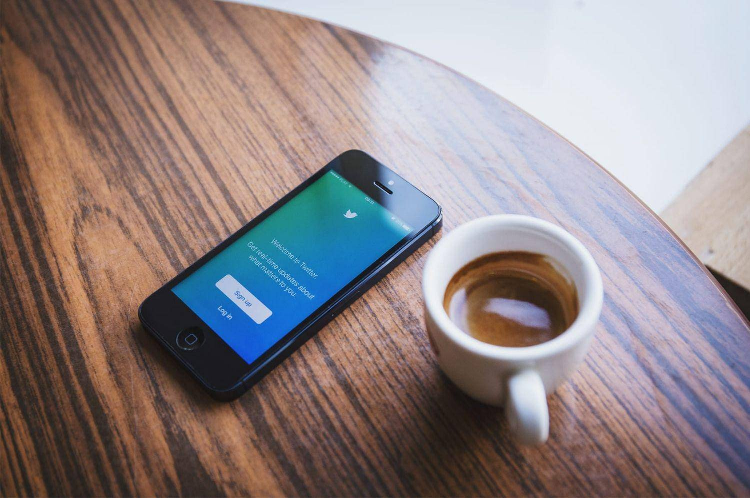 Social Media graphics on a phone with a cup of coffee on table
